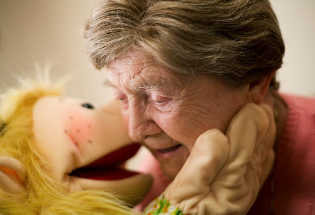 eine Klappmaulpuppe (Living Puppet) in Spiel und Kontakt mit einer Seniorin